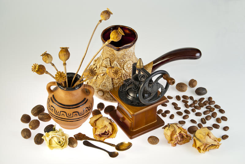 Coffee still life of ancient utensils and grains. The composition of the ancient household utensils scattered on the background of the coffee beans and nutmeg stock images