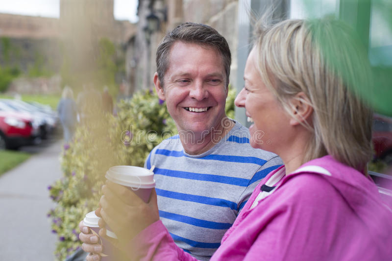 Coffee Stop. Mature couple laughing as they sit outside and drink hot drinks out of takeaway cups. They are wearing casual clothing and look very happy stock image