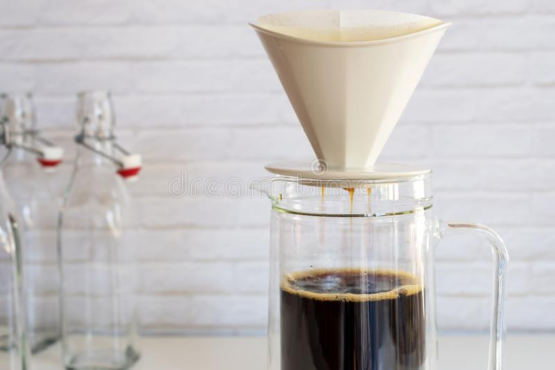 Coffee strained with coffee filter into the glass jar ,how to ma royalty free stock images