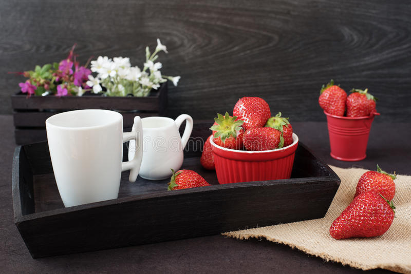 Coffee and strawberries on wooden tray over black table. White and purple flowers in a decorative wooden crate. Black background stock image