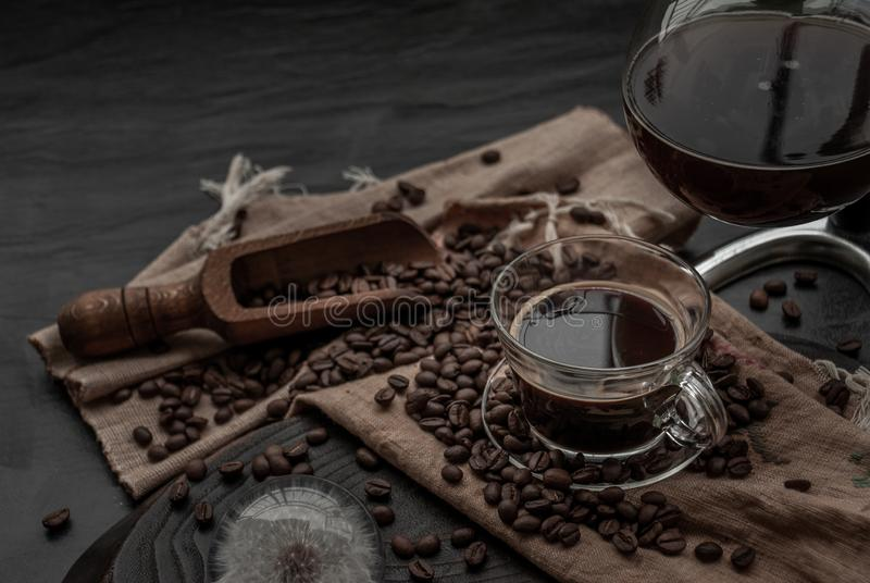 Cup of coffee and coffee beans roating with old wooden scoop and coffee beans around on the wooden and dark stone background. royalty free stock image