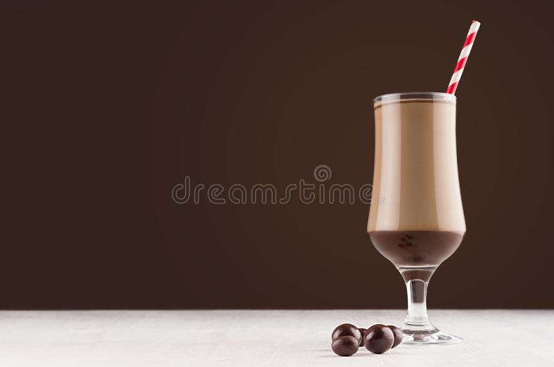 Coffee sweet dessert in goblet with chocolate candies and red striped straw in dark brown modern restaurant interior, copy space. Coffee sweet dessert in goblet stock photo