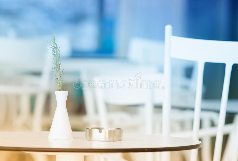 Coffee table with ashtray and vase. Bright image of ashtray and vase with rosemary on white coffee table and chairs at bar stock photo