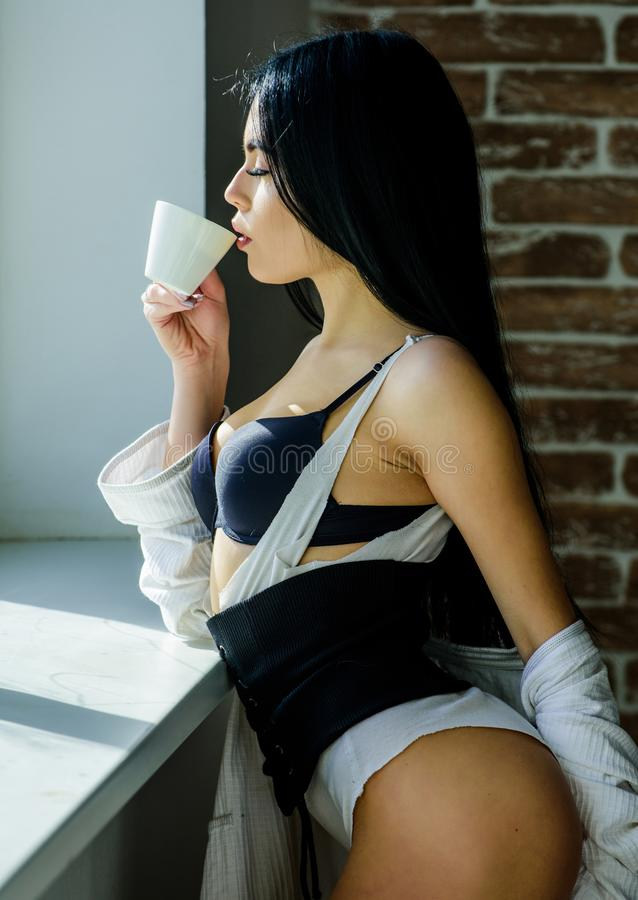 Coffee, take me away. Sensual girl drinking her favorite morning coffee. Pretty woman drinking fresh hot coffee at stock photography