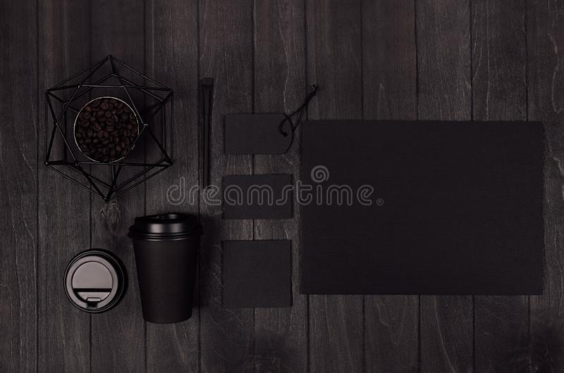 Coffee takeaway set mockup for brand - black paper cup, blank paper, card, label, decoration, coffee beans on dark black wood. Coffee takeaway set mockup for stock images