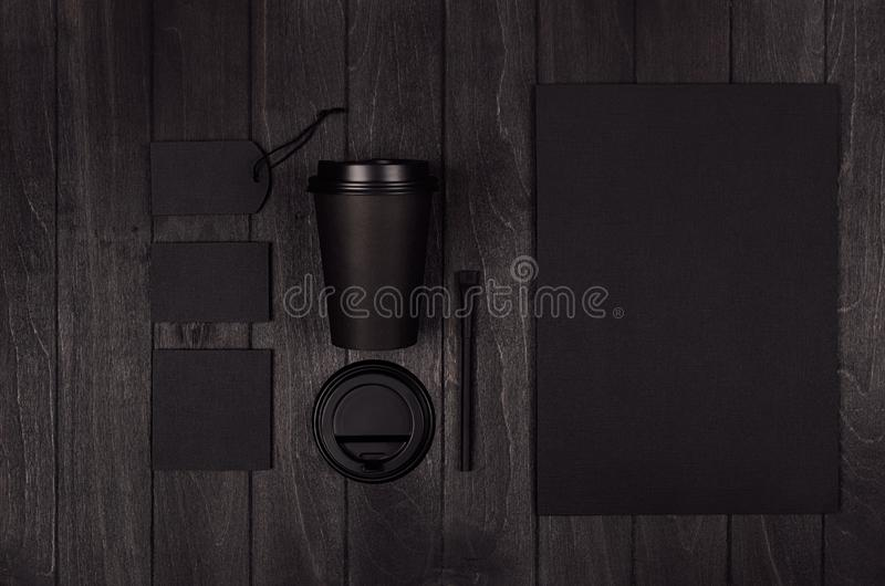 Coffee takeaway set mockup for brand - black paper cup, blank paper, card, label, sugar, cap on dark black wood board, copy space. Coffee takeaway set mockup royalty free stock images