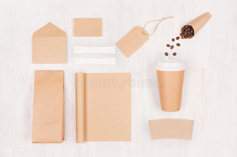 Coffee takeaway set mockup for brand - brown paper cup, blank notebook, packet, label, stationery, coffee beans, sugar on wood. royalty free stock photo
