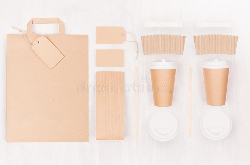 Coffee takeaway set mockup for brand - two brown paper cups with blank bag, card, label, packet, sugar, cap on white wood board. Coffee takeaway set mockup for royalty free stock images