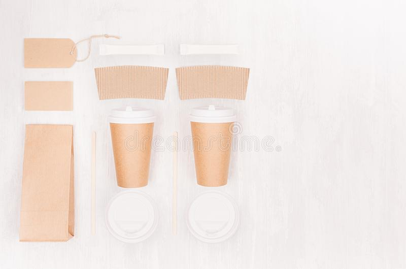 Coffee takeaway set mockup for brand - two brown paper cups with blank card, label, packet, cap, sugar, copy space on white wood. Coffee takeaway set mockup for stock image