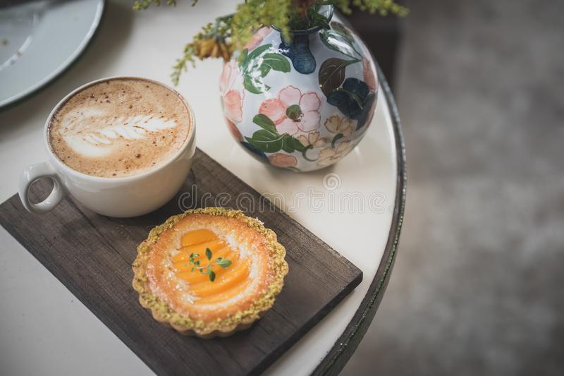 Coffee and tart. Hot latte coffee and peach tart for afternoon break stock images