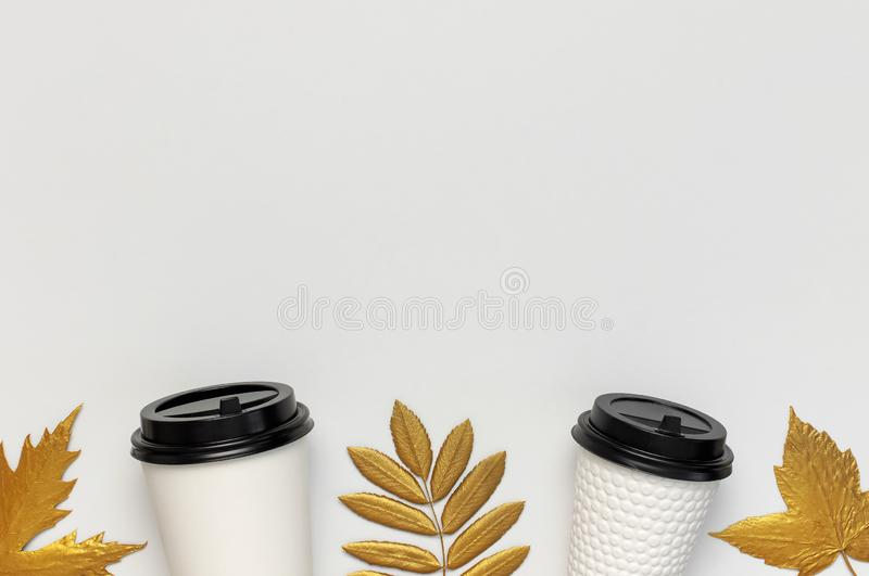 Coffee or tea paper cups, golden autumn leaves on light gray background top view flat lay. Take away coffee cup, mockup. Coffee. Love, layout for design. Fall stock image