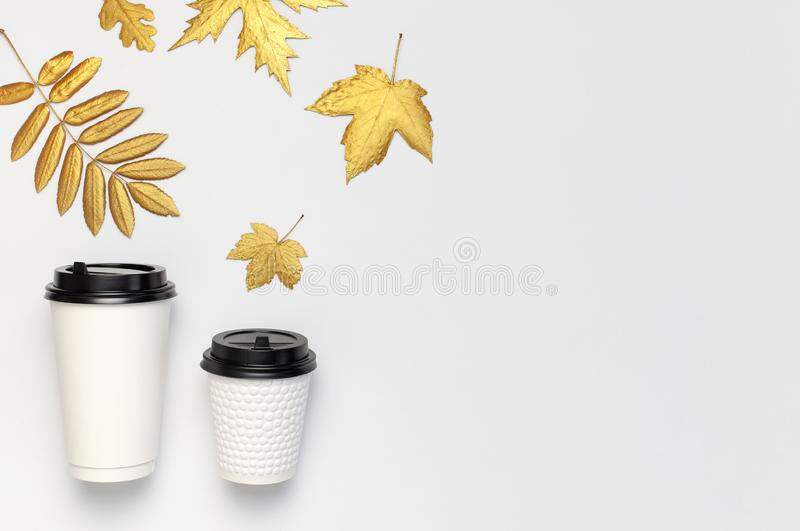Coffee or tea paper cups, golden autumn leaves on light gray background top view flat lay. Take away coffee cup, mockup. Coffee. Love, layout for design. Fall stock photography