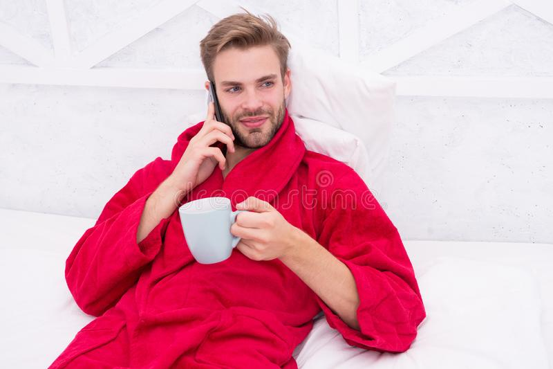 Coffee and technology have gone hand in hand. Young man using mobile technology in bed. Handsome guy talking on phone royalty free stock photography