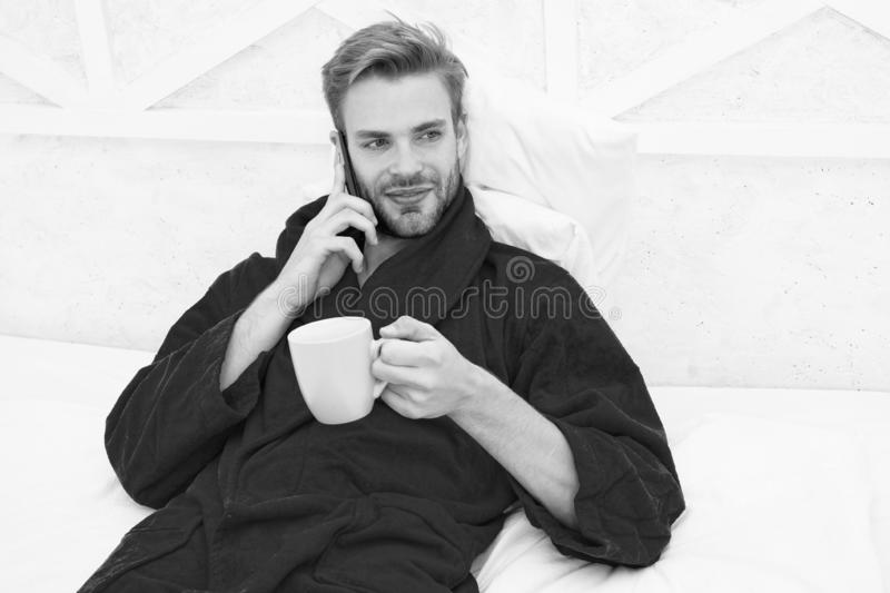 Coffee and technology have gone hand in hand. Young man using mobile technology in bed. Handsome guy talking on phone stock photography