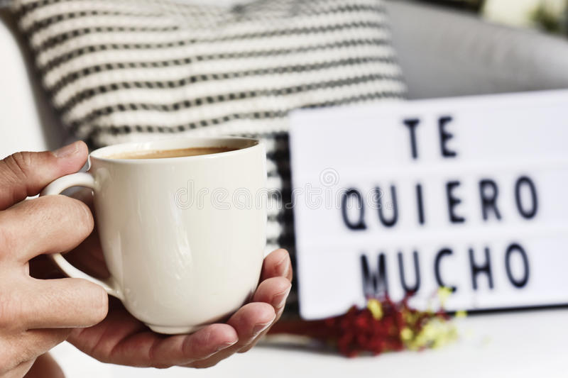 Coffee and text I love you so much in Spanish. Closeup of a young man with a white ceramic cup with coffee in his hand and a lightbox in the background with the royalty free stock images