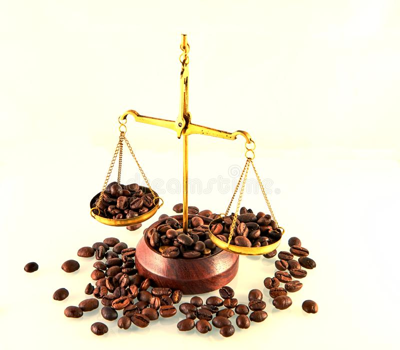 Coffee theme with brass scales still life on white background. Coffee beans on the scales, aroma, balance, beverage, brown, cafe, caffeine, choice, closeup royalty free stock image