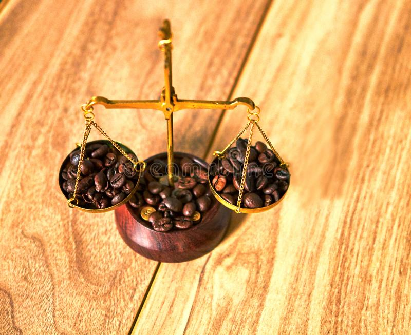 Coffee theme with brass scales still life on a wooden table. Coffee beans on the scales royalty free stock photography