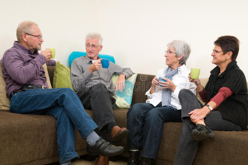 Coffee Time. Group of four seniors drinking coffee, chatting and having a great familytime together