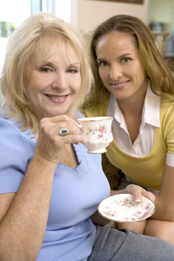 Coffee time. Mother and daughter enjoying coffee with their dog stock photography