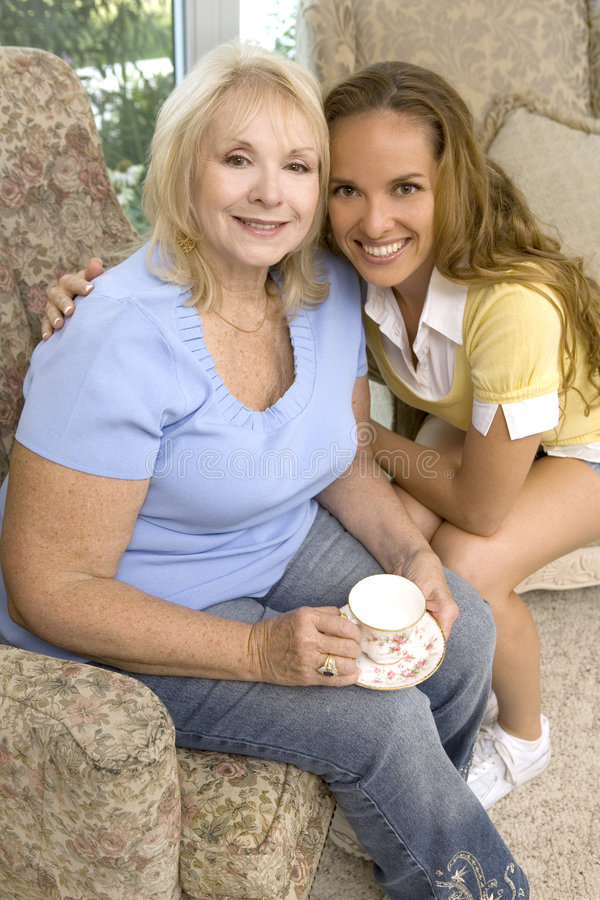 Coffee time. Mother and daughter enjoying coffee with their dog royalty free stock image