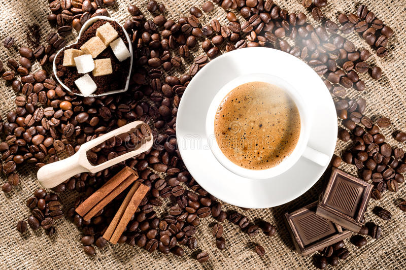 Coffee time concept. Cup of coffee with steam, coffee beans, chocolate pieces, cinnamon sticks, white and brown sugar, and scoop on burlap background stock images