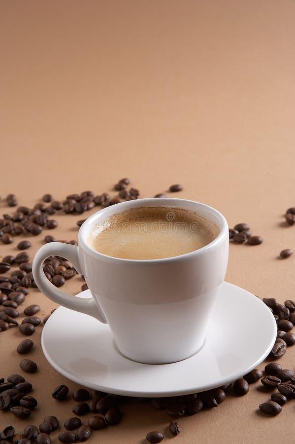 Coffee time - Kaffeezeit. Coffe cup with coffee beans on brown background - Kaffeetasse mit Kaffeebohnen vor braunem Hintergrund royalty free stock photo