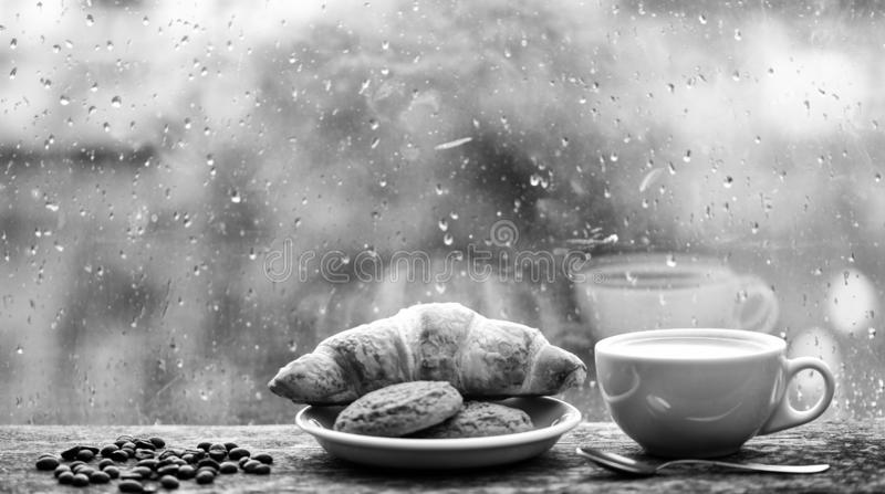 Coffee time on rainy day. Fresh brewed coffee in white cup or mug on windowsill. Wet glass window and cup of hot. Caffeine beverage. Coffee drink with croissant royalty free stock photo