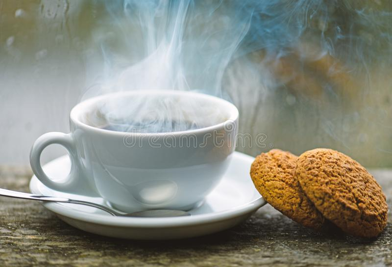 Coffee time on rainy day. Fresh brewed coffee in white cup or mug on windowsill. Wet glass window and cup of hot stock photos