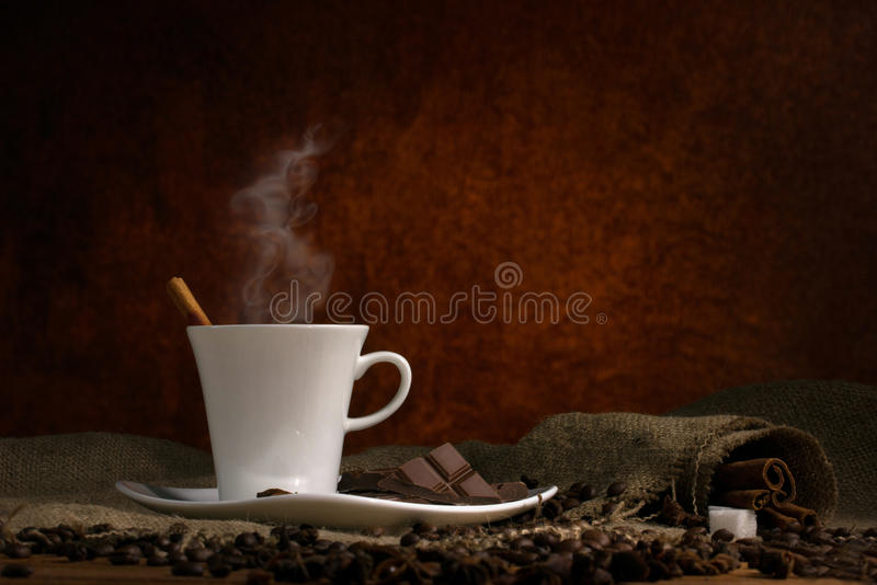 Coffee time. Coffee with steam in white cup on saucer, and cubes sugar on burlap wooden table on dark brown background stock photo