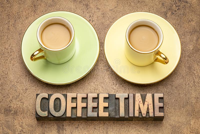Coffee time word abstract in wood type. Coffee time word abstract in vintage letterpress wood type with two cups of coffee royalty free stock image