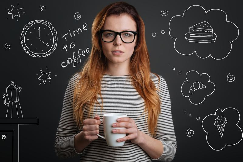 Calm student drinking coffee and choosing a tasty dessert. Coffee time. Young calm beautiful student standing with a cup of hot tasty coffee and looking stock photography
