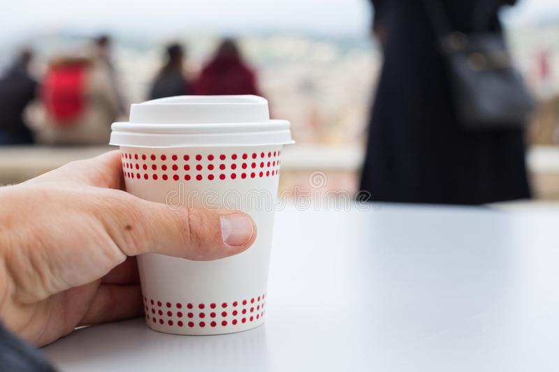 Coffee to go. Close up picture of human hand holding coffee to go stock photography