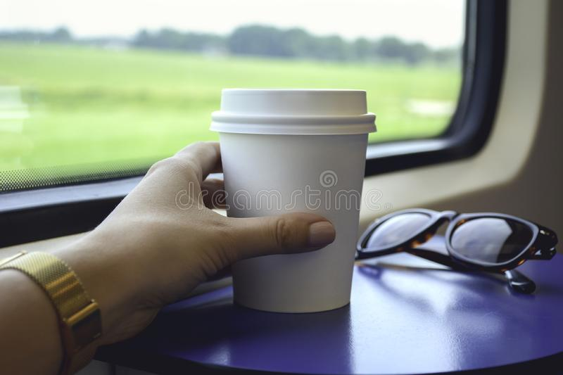 Coffee to go. Female hand holding a paper cup of coffee to takeaway stock image