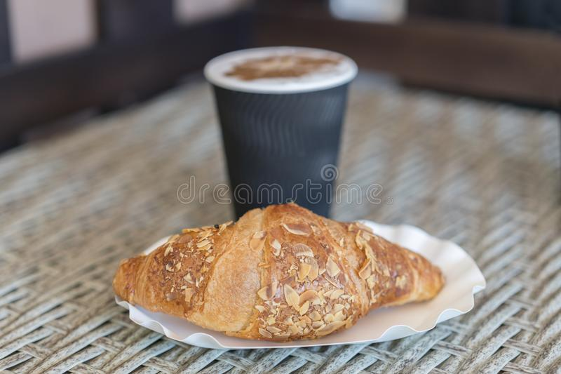 Coffee to go in a paper cup with croissants on wooden table, . Coffee to go in a paper cup with croissants, close up. selective fo. Cus royalty free stock images