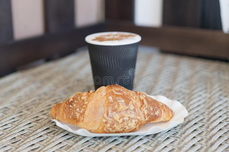 Coffee to go in a paper cup with croissants on wooden table, . Coffee to go in a paper cup with croissants, close up. selective fo. Cus stock photos