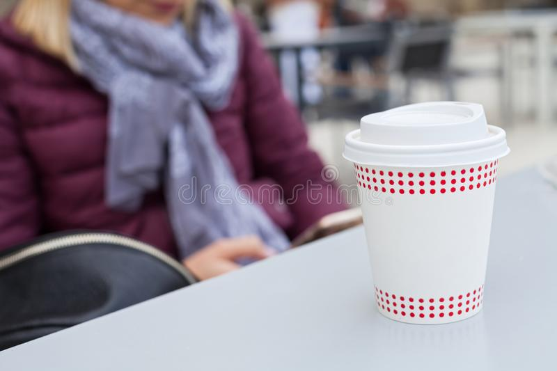 Coffee to go. In white paper cup on a table, young woman texting on the phone in the background stock photography