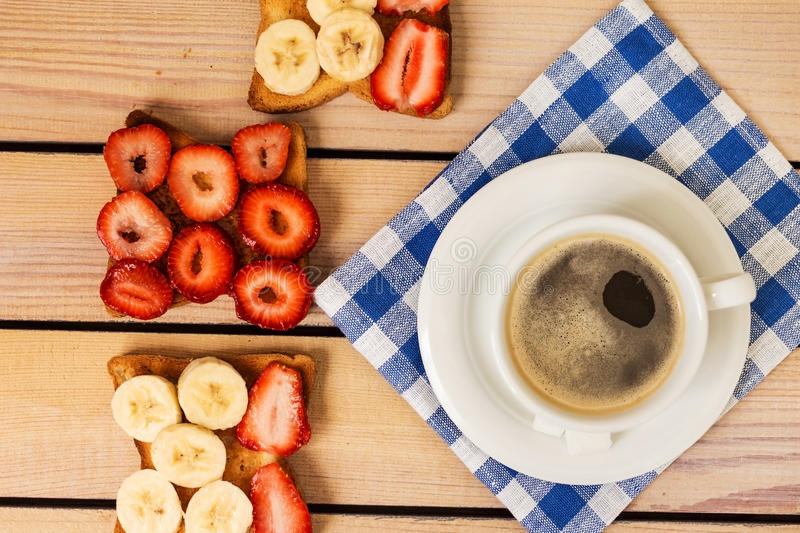 Coffee and toast with strawberries and bananas stock photos