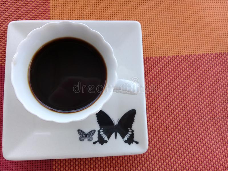 Coffee on top of a saucer with butterfly design royalty free stock photo