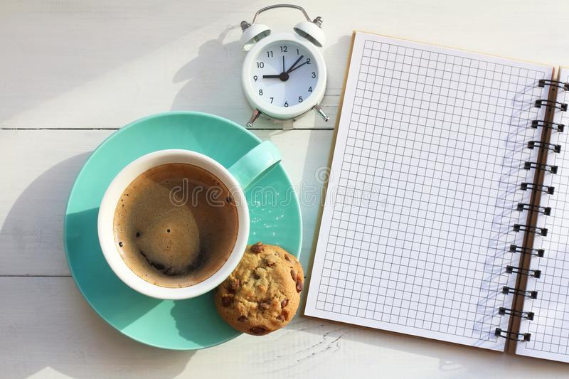 Coffee in a turquoise mug and cookies near a notebook on a white table and the white alarm clock the top view.  stock photo