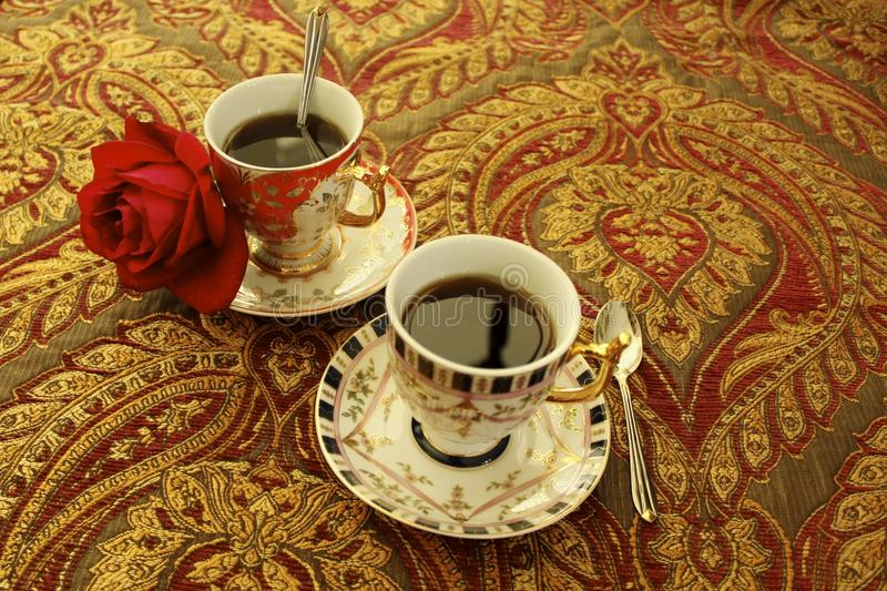 Coffee victorian cups. Victorian coffee cups for two and red rose royalty free stock photography