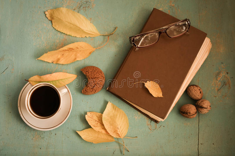 Coffee, vintage book, glasses and autumn leaves on wood background - relax or retirement concept. Hot coffee, vintage book, glasses and autumn leaves on wood royalty free stock images