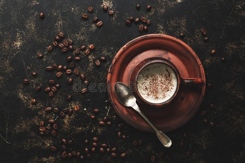 Coffee in a vintage brown ceramic cup on a dark grunge background with roasted coffee beans. Top view, copy space royalty free stock image