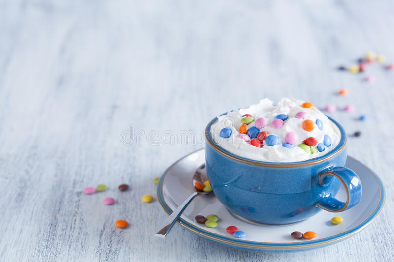 Coffee with whipped cream and colorful chocolate drops royalty free stock images