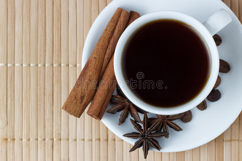 Coffee in a white cup with anise and cinnamon sticks on a bamboo background royalty free stock photography