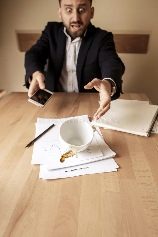 Coffee in white cup spilling on the table in the morning working day at office table. The businessman and coffee in white cup spilling in slow motion or movement stock photography