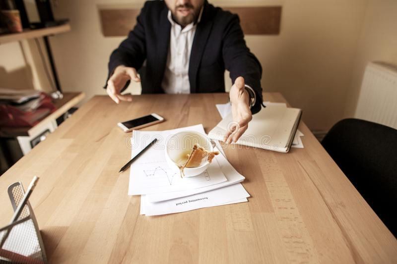 Coffee in white cup spilling on the table in the morning working day at office table. The businessman and coffee in white cup spilling in slow motion or movement royalty free stock image