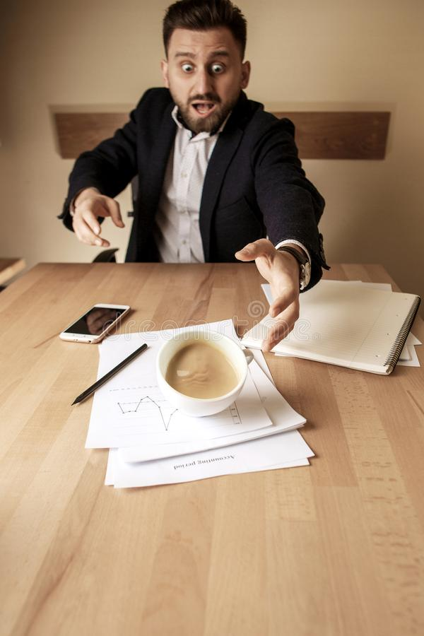 Coffee in white cup spilling on the table in the morning working day at office table. The businessman and coffee in white cup spilling in slow motion or movement stock photos