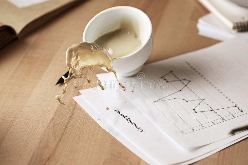 Coffee in white cup spilling on the table in the morning working day at office table. Coffee in white cup spilling in slow motion or movement on the table with royalty free stock images