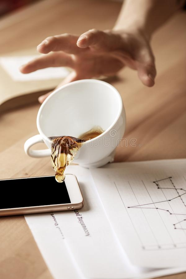 Coffee in white cup spilling on the table in the morning working day at office table. The male hands and coffee in white cup spilling in slow motion or movement stock image