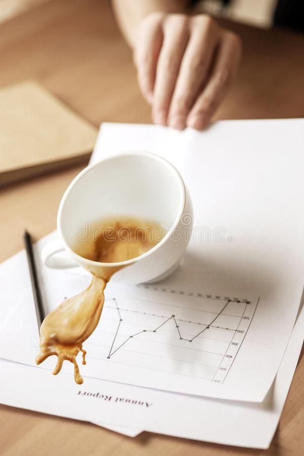 Coffee in white cup spilling on the table in the morning working day at office table. The male hands and coffee in white cup spilling in slow motion or movement stock photo